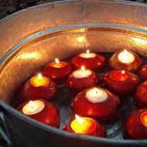 Świeczniki z jabłek umieszczone w wiaderku z wodą